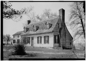 black and white photo of house with prominant chimney several windows with shutters on lower lever and in dormers on second floor